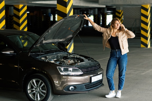 Bezorgde vrouwelijke bestuurder in spijkerbroek en windjack, die om hulp roept op de parkeerplaats om te helpen bij het defect raken van de auto