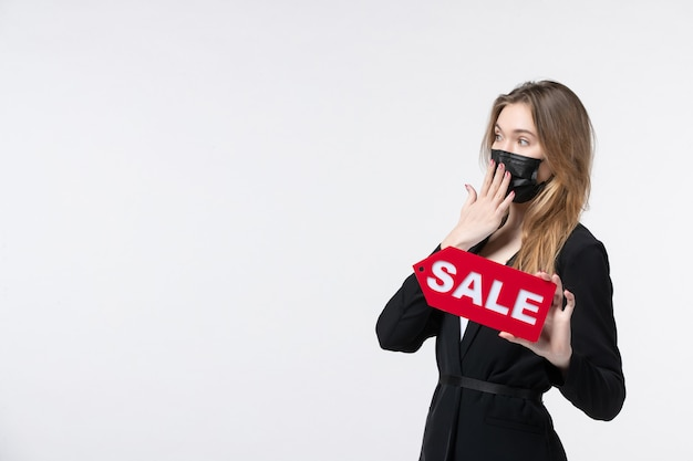 Bezorgde vrouwelijke ondernemer in pak die haar medisch masker draagt en verkoop toont op geïsoleerde witte muur