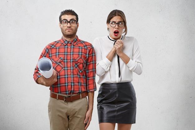 Bezorgde vrouwelijke stagiair heeft angstige uitdrukking als kijkt naar strikte mannelijke leraar leert details te ontwerpen, wil kennis verbeteren
