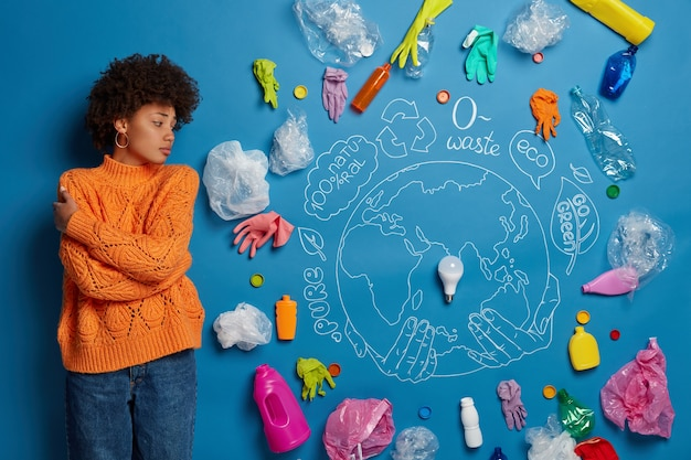 Bezorgde vrouwelijke vrijwilliger omhelst zichzelf en draait zich om, kijkt droevig naar plastic afval dat een ernstig milieuprobleem en ecologische vervuiling aantoont