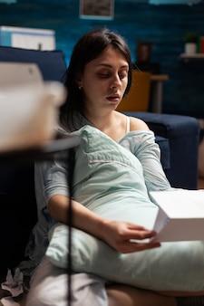 Bezorgde wanhopige gefrustreerde depressieve jonge vrouw die factuurbank leest