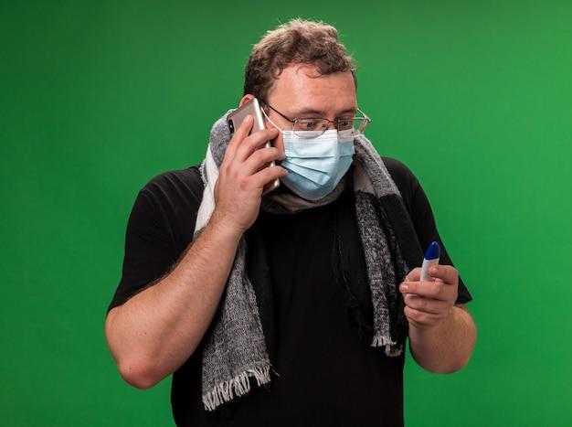 Bezorgde zieke man van middelbare leeftijd met een medisch masker en sjaal spreekt aan de telefoon en kijkt naar de thermometer in zijn hand