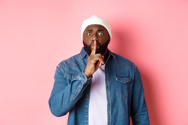 Bezorgde zwarte man die vraagt om te zwijgen, geheim te delen en naar je te zwijgen, vinger tegen de lippen te houden en nerveus naar de camera te staren, roze achtergrond