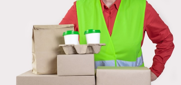 Bezorgen is in een groen vest met daarin papieren dozen en een container om mee te nemen met twee witte kopjes koffie.