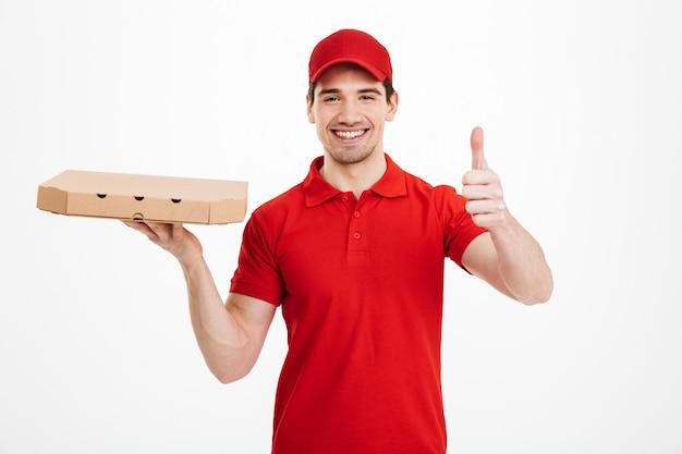 Bezorger 25j in rood t-shirt en pet met afhaalmaaltijden doos met pizza en gebaren duim omhoog, geïsoleerd over witte ruimte