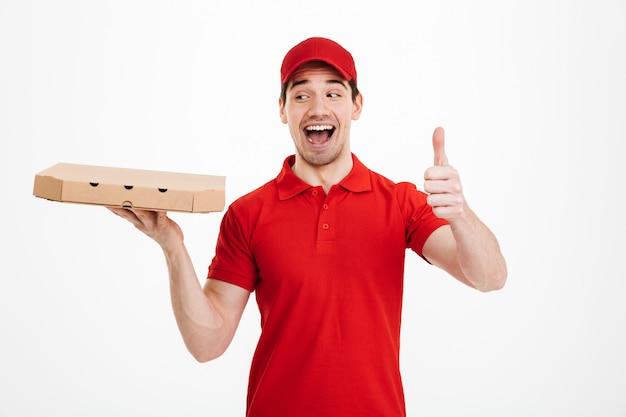 Bezorger 25j in rood t-shirt en pet met afhaalmaaltijden kartonnen doos met pizza en gebaren duim omhoog met perfecte glimlach, geïsoleerd over witte ruimte