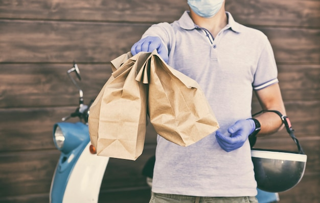 Bezorger bezorgt eten aan de klant met een bromfiets