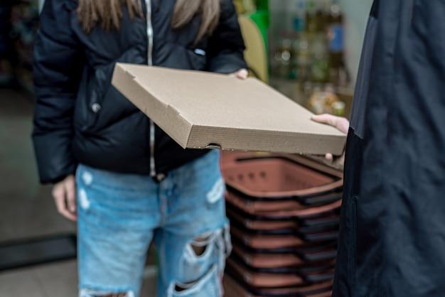 Bezorger bezorgt voedsel aan het huis van de klant, met een rode zak