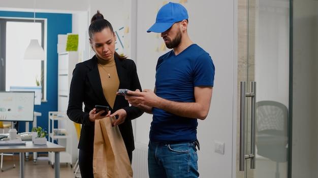 Bezorger die afhaalmaaltijden meeneemt naar zakenvrouw in opstartend bedrijfskantoor