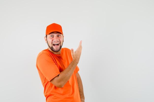 Bezorger die arm opheft in extatisch gebaar in oranje t-shirt, pet en er gelukkig uitziet, vooraanzicht.