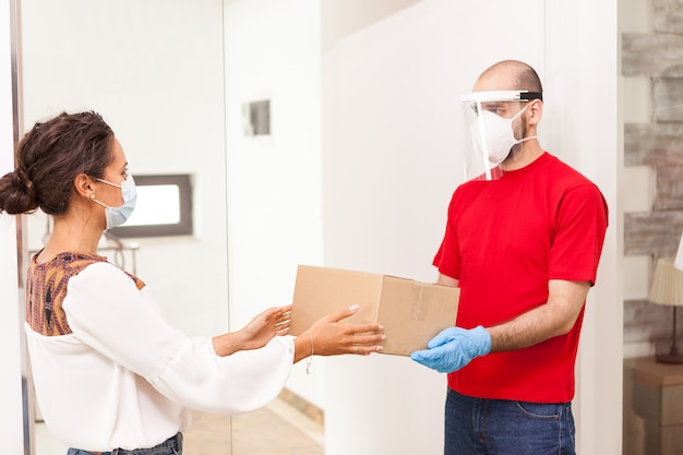Bezorger die bescherming draagt en vrouwelijke klant haar bestelling geeft.