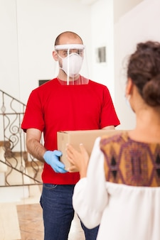 Bezorger die beschermingsmasker draagt dat pakket voor vrouwelijke klant houdt.