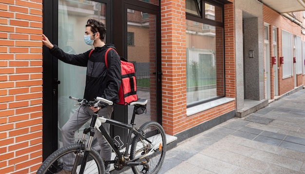 Bezorger die de portier belt, een gezichtsmasker draagt, een rode zak vasthoudt om het pakket af te leveren