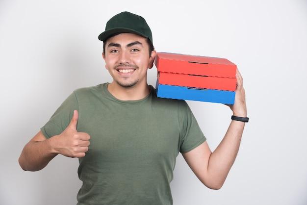 Bezorger die drie dozen pizza houdt en duimen op witte achtergrond toont.