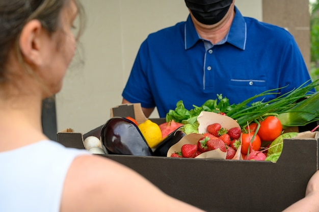 Bezorger die een gezichtsmasker draagt en een doos met groenten houdt