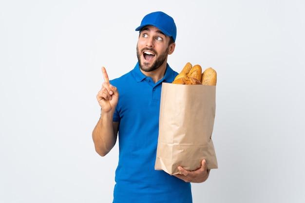 Bezorger die een zak vol brood houdt dat op witte muur wordt geïsoleerd met de bedoeling de oplossing te realiseren terwijl hij een vinger opheft