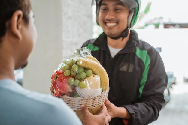 Bezorger die fruitpakket levert