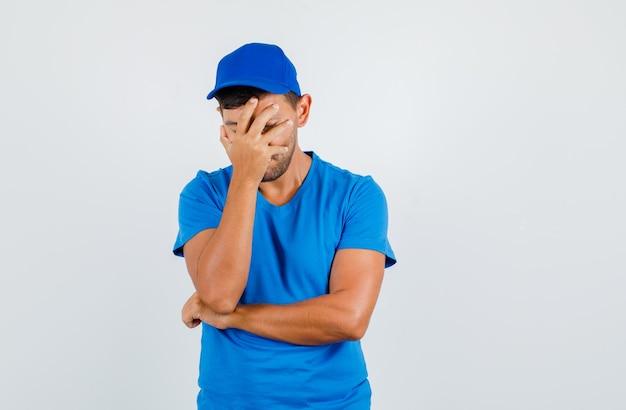 Bezorger die gezicht bedekt met hand in blauw t-shirt, pet en peinzend kijkt.