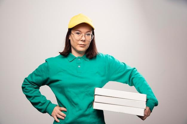 Bezorger die karton van pizza op een wit draagt. hoge kwaliteit foto