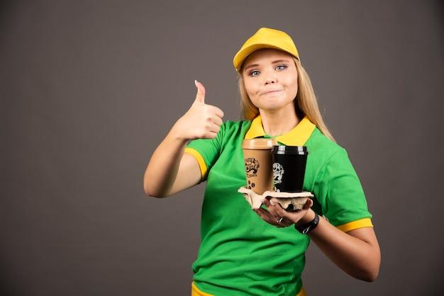 Bezorger die kopjes koffie vasthoudt en duim laat zien.