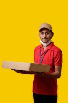 Bezorger die medisch masker draagt en doos in handen houdt. bezorger. veilig leveringsconcept.
