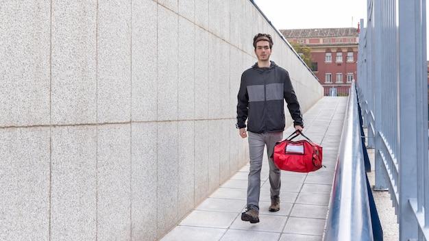 Bezorger die met rode zak loopt om een levering aan huis te doen