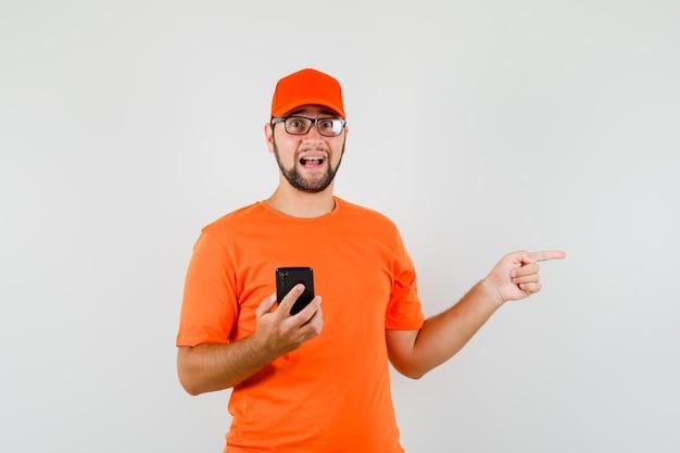 Bezorger die mobiele telefoon vasthoudt en naar de zijkant wijst in oranje t-shirt, pet, vooraanzicht.