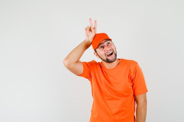 Bezorger die v-teken boven het hoofd toont in oranje t-shirt, pet en er grappig uitziet. vooraanzicht.