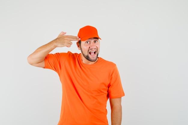 Bezorger die zelfmoordgebaar maakt in oranje t-shirt, pet en er geamuseerd uitziet. vooraanzicht.