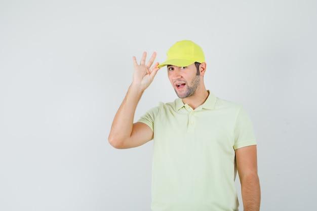 Bezorger die zijn pet in geel uniform vasthoudt en elegant, vooraanzicht kijkt.
