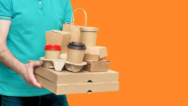 Bezorger draagt verschillende afhaalmaaltijden, pizzadoos, koffiekopjes in houder en papieren zak op oranje achtergrond. ruimte kopiëren