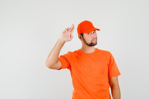Bezorger gebaart met twee vingers in oranje t-shirt, pet en ziet er zelfverzekerd uit. vooraanzicht.