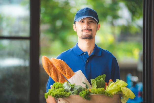 Bezorger geeft de tas van de kruidenierswinkel aan de vrouw aan de voorkant van haar huis