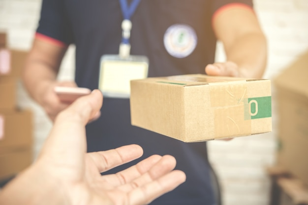 Bezorger glimlacht en houdt een kartonnen doos