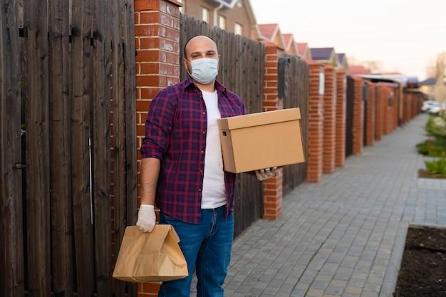 Bezorger houdt een kartonnen doos en draagt een gezichtsmasker voor coronaviruspreventie
