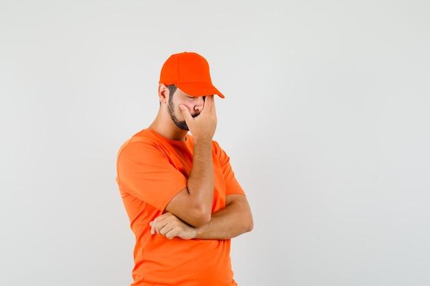 Bezorger houdt hand op gezicht in oranje t-shirt, pet en kijkt berouwvol. vooraanzicht.