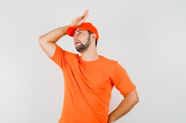 Bezorger houdt hand op hoofd in t-shirt, pet en kijkt geïrriteerd, vooraanzicht.