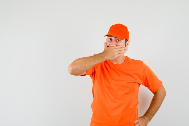 Bezorger houdt hand op mond in oranje t-shirt, pet en kijkt opgewonden. vooraanzicht.