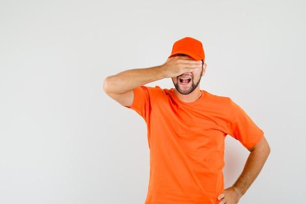 Bezorger houdt hand op ogen in oranje t-shirt, pet en kijkt opgewonden, vooraanzicht.
