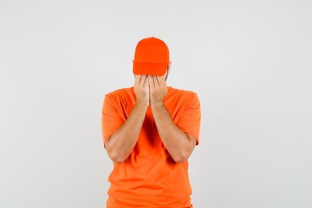 Bezorger houdt handen op gezicht in oranje t-shirt, pet en kijkt boos, vooraanzicht.