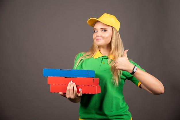 Bezorger houdt karton van pizza vast en toont duim.