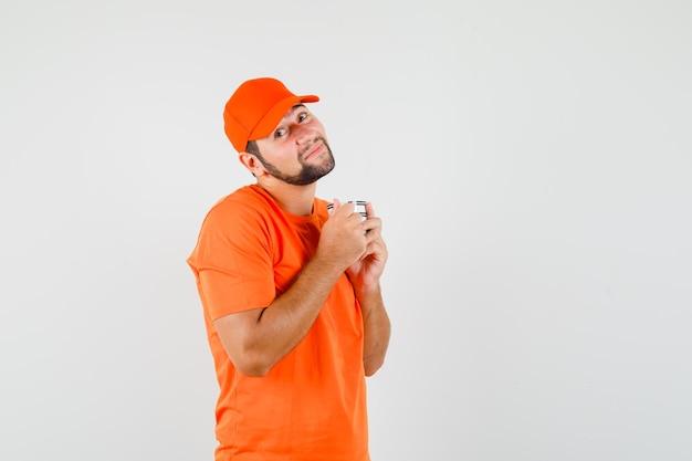 Bezorger houdt kopje drank in oranje t-shirt, pet en ziet er schattig uit. vooraanzicht.