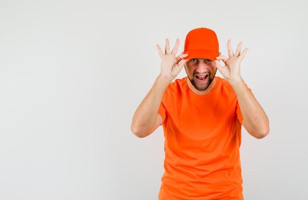 Bezorger houdt vingers op zijn pet in oranje t-shirt en ziet er zelfverzekerd uit, vooraanzicht.