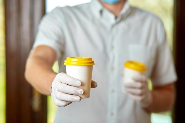 Bezorger in beschermend masker en handschoenen, werknemer houden afhaalmaaltijden kopje koffie, coronavirus