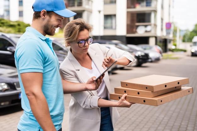 Bezorger in blauw uniform bezorgt pizza bij een vrouw clie