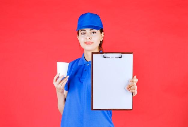 Bezorger in blauwe outfit die leeg klembord toont en plastic beker vasthoudt.