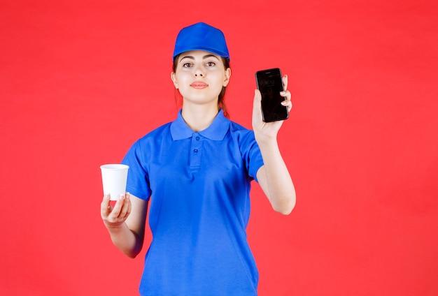 Bezorger in blauwe outfit met mobiele telefoon en kopje thee op rood.