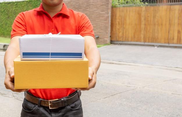 Bezorger in de rode eenvormige koerier van het holdingspakket met pakket. levering concept