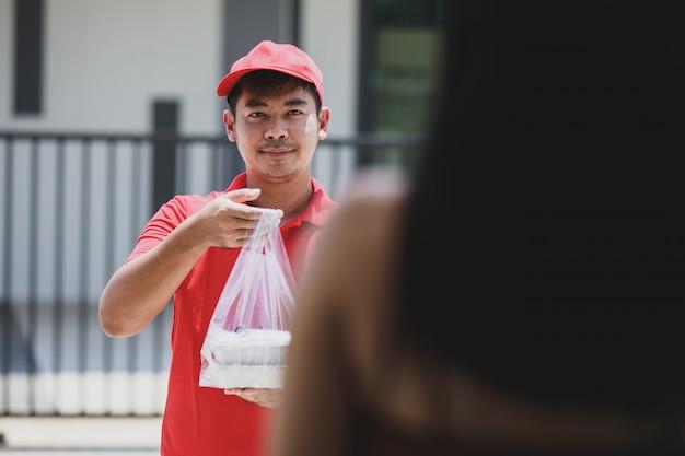 Bezorger in een rood t-shirt met voedselpakket