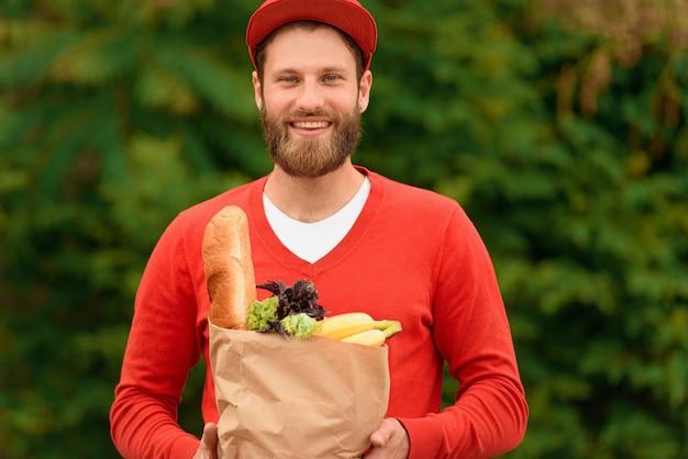 Bezorger in een rood uniform met een papieren eco-tas met boodschappen in zijn handen.